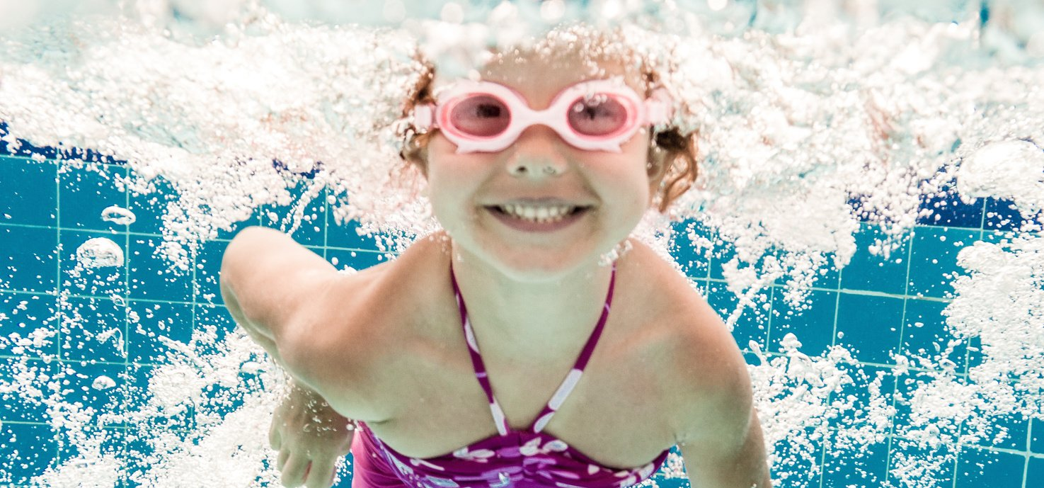 Girl smiles, swimming under water in the pool.